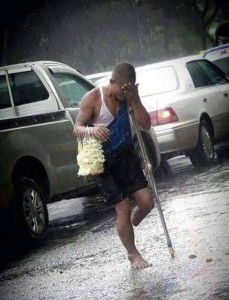 This disabled man sells 'Sampaguita' flowers in the streets while heavy rain is pouring
